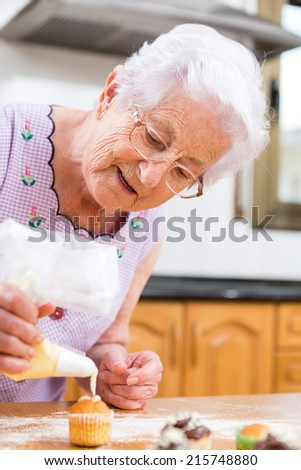 Woman Decorating Cupcakes old woman making decorating cupcakes stock photo 215748850