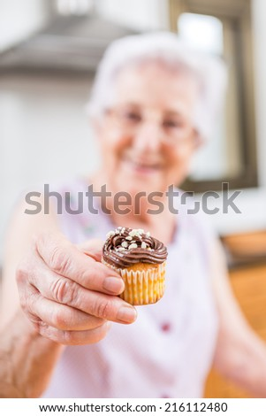 old woman making and decorating cupcakes - Woman Decorating Cupcakes