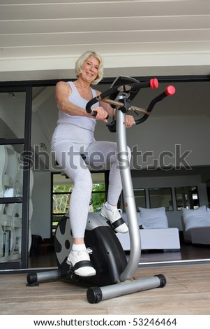Old woman making of the exercise bike