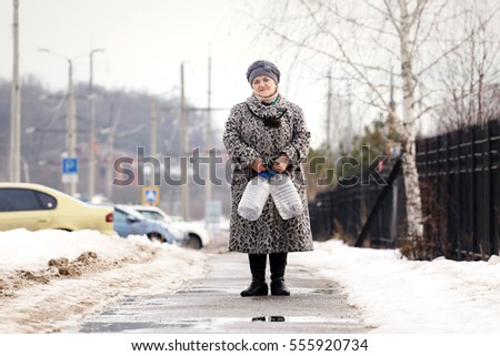Old woman on the street with bottles