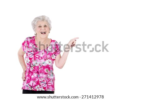 Old woman pointing to a side with her finger against a white background - stock photo