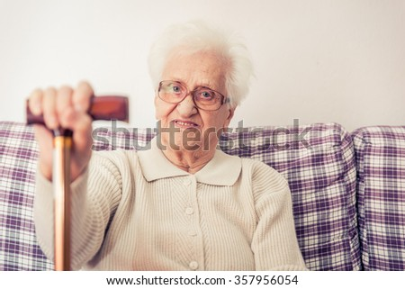 Old woman portrait. Woman sitting on the couch and holding a wood cane. Concept about aging, people and lifestyle - stock photo