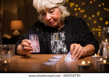 Old woman predicting future from tarot cards - stock photo