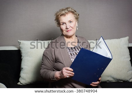 old woman reads a folder with documents