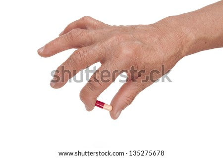 Old Woman's Hand Deformed From Rheumatoid Arthritis Holding Pill Isolated