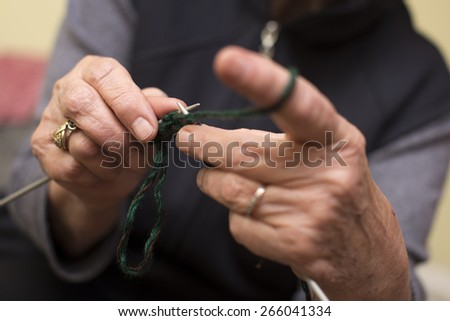 old woman's hand knitting with green thread