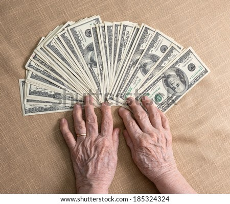 Old woman's hands and dollar bills - stock photo