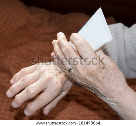 Old woman's hands applying cream - stock photo