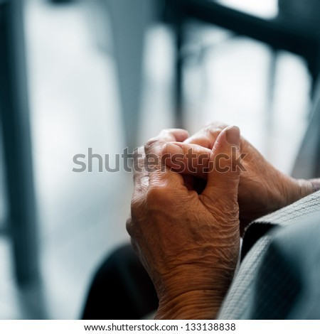 Old woman's hands clasped praying. - stock photo