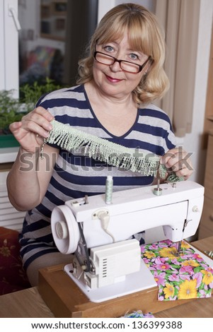 Old woman sews on the sewing machine