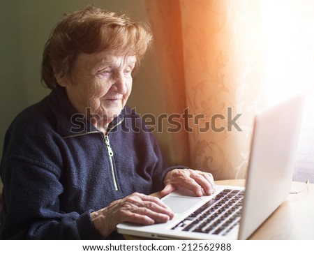 Old woman sing laptop computer at home. - stock photo