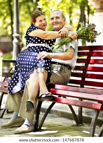 Old woman sit in hand of senior man. Outdoor. - stock photo