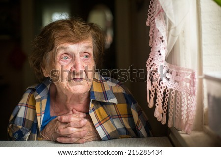 Old woman sitting at a table in his house, with a worried expression on his face. - stock photo