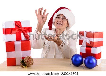 old woman sitting at the table with gift box. Isolated on white background - stock photo