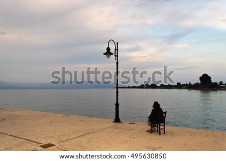 Old woman sitting lonely looking at the sunset against a dramatic sky.