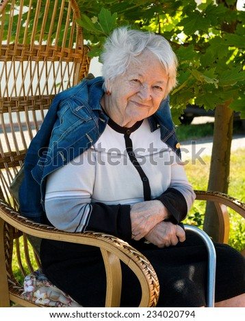 Old woman sitting on a chair with a cane in the garden