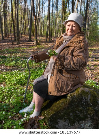 Old woman sitting on a stump on nature background