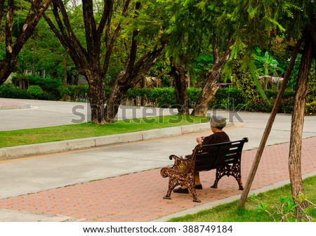 Old  woman sitting on bench at park - stock photo