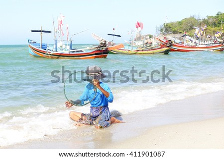Old woman sitting working on wet sand on the beach with strong wave and colorful boat in the sea background:select focus with shallow depth of field.