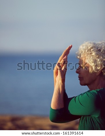 Old woman stretching her arms by the sea. Senior caucasian woman exercising on beach in morning. Fitness and healthy lifestyle concept. - stock photo