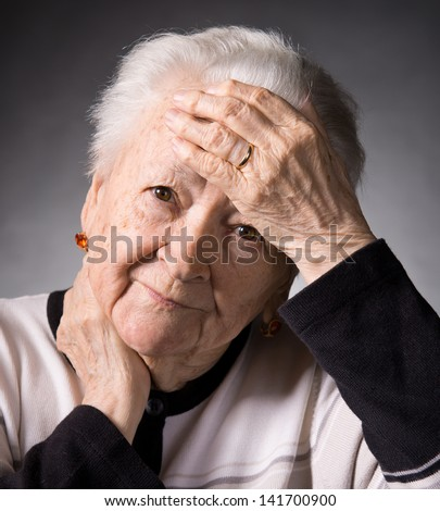 Old woman suffering from headache on a gray background - stock photo