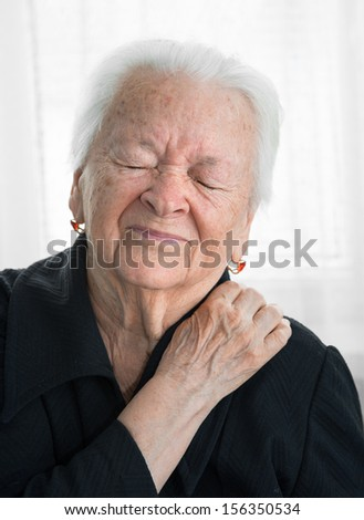 Old woman suffering from shoulder ache