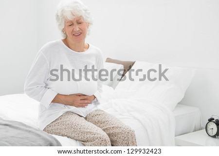 Old woman suffering with belly pain in the bedroom