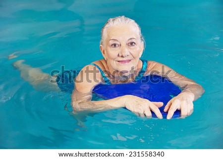 Old woman swimming in water with kickboard in a hotel pool - stock photo