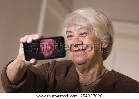 Old woman taking a selfie - stock photo