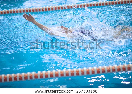 Old woman training to swim the backstroke - stock photo