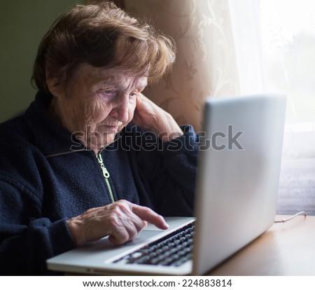 Old woman typing on laptop keyboard. - stock photo