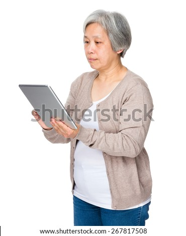 Old woman use of digital tablet - stock photo