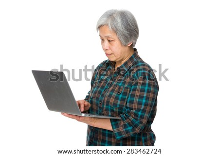 Old woman use of notebook computer - stock photo