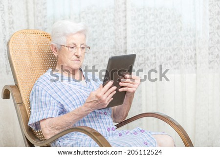 Old woman using a digital tablet on chair