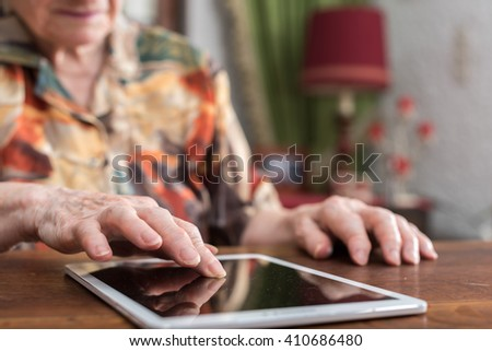 Old woman using tablet at home
