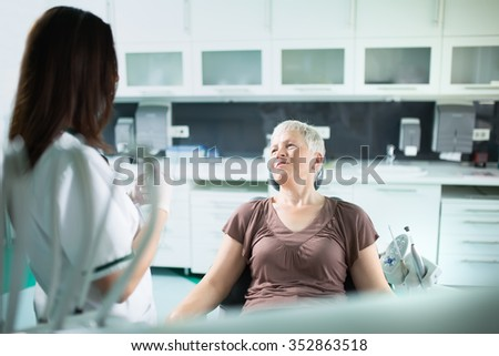 Old woman visiting the dentist taking care of her teeth.Dentist doctor talking to a senior woman patient.Dental care for elder.Prosthodontics and oral protesis - stock photo