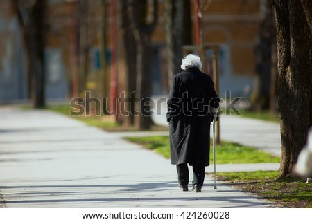 Old woman walking down the street with walking stick