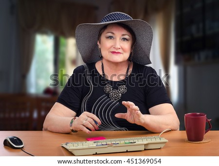 Old woman wants to end the on-line conversation. Portrait older woman in dark grey hat sits at the wooden desk on dark blurry background. She looks at camera. There are grey keyboard and ceramic mug