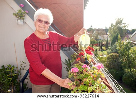 old woman watering flowers on the balcony - stock photo