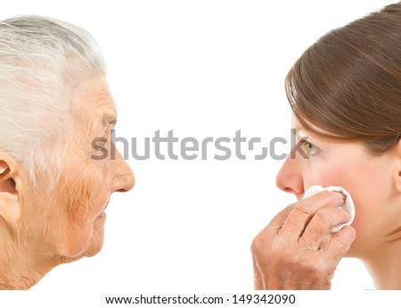 old woman wiping off the face of a young one with a makeup pad - stock photo