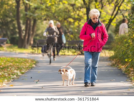 Old woman with a dog in autumn park