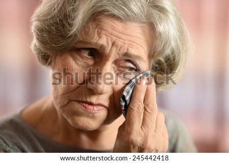 Old woman with a handkerchief at home - stock photo