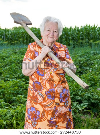 Old woman with a shovel in the garden - stock photo
