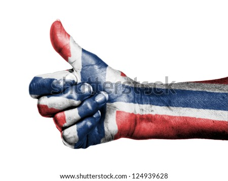 Old woman with arthritis giving the thumbs up sign, wrapped in flag pattern, Norway - stock photo
