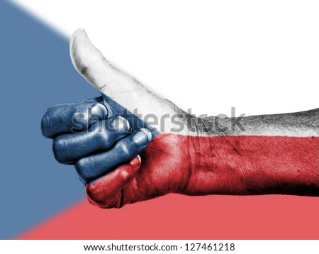 Old woman with arthritis giving the thumbs up sign, wrapped in flag pattern, The Czech Republic - stock photo