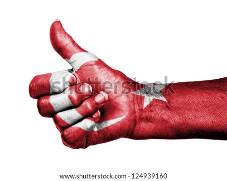 Old woman with arthritis giving the thumbs up sign, wrapped in flag pattern, Turkey - stock photo
