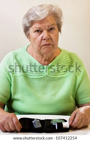 old woman with equipment of blood sugar test