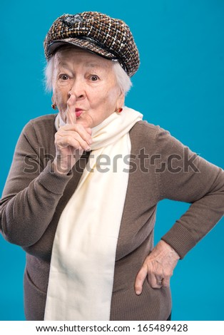 Old woman with finger on lips asking for silence on a blue background - stock photo