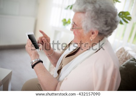 Old woman with glasses holding a smartphone - stock photo
