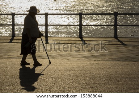 Old woman with hat and cane walking at sunset - stock photo